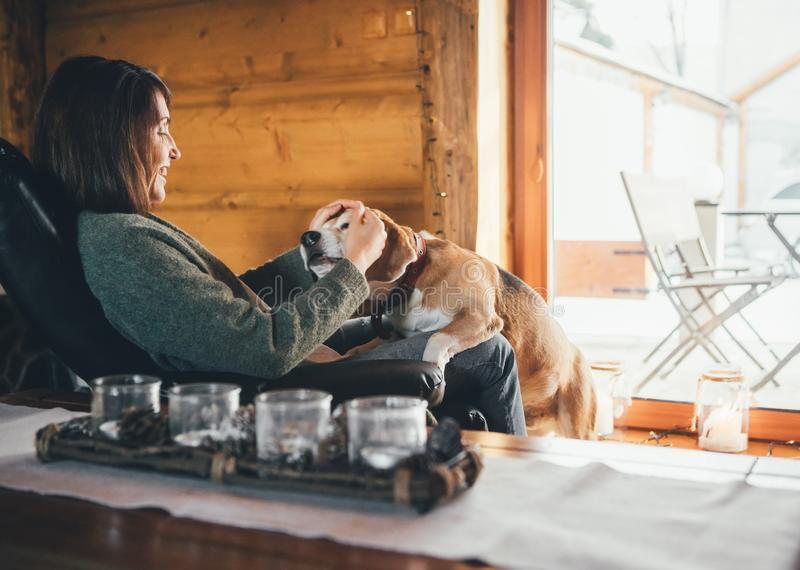 Tender scene with woman and her beagle dog in comfortable cozy country home. Countryside vacation with pets royalty free stock photography