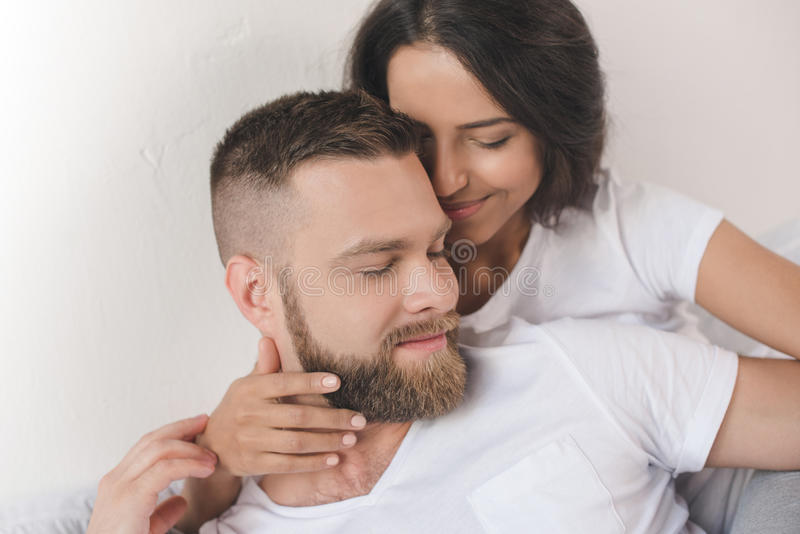 Tender smiling couple embracing and lying on bed at home royalty free stock images