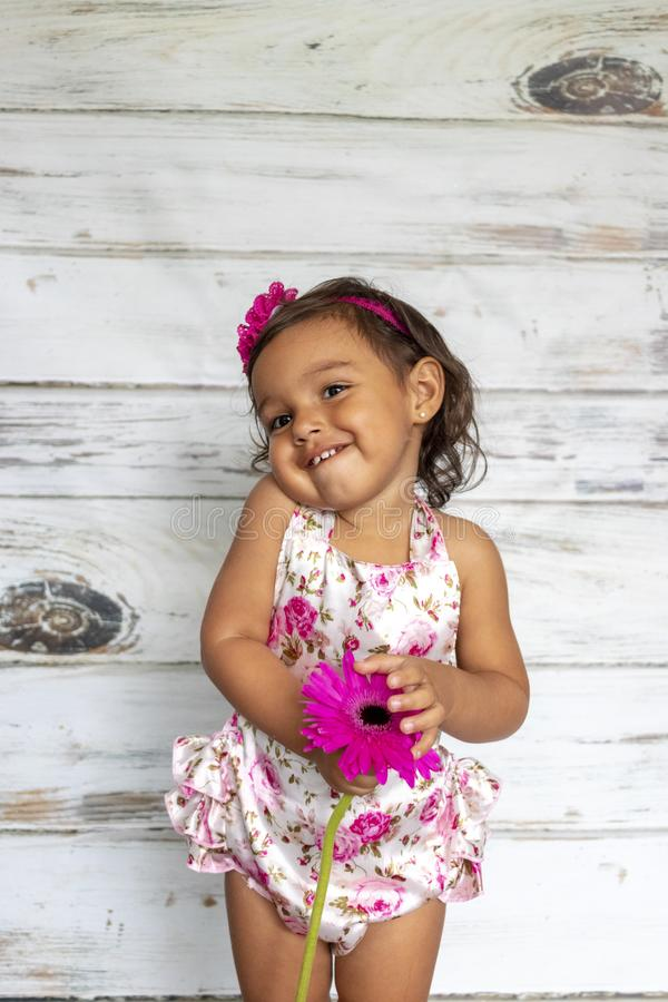 Tender smiling toddler. With a flower in her hands stock photo