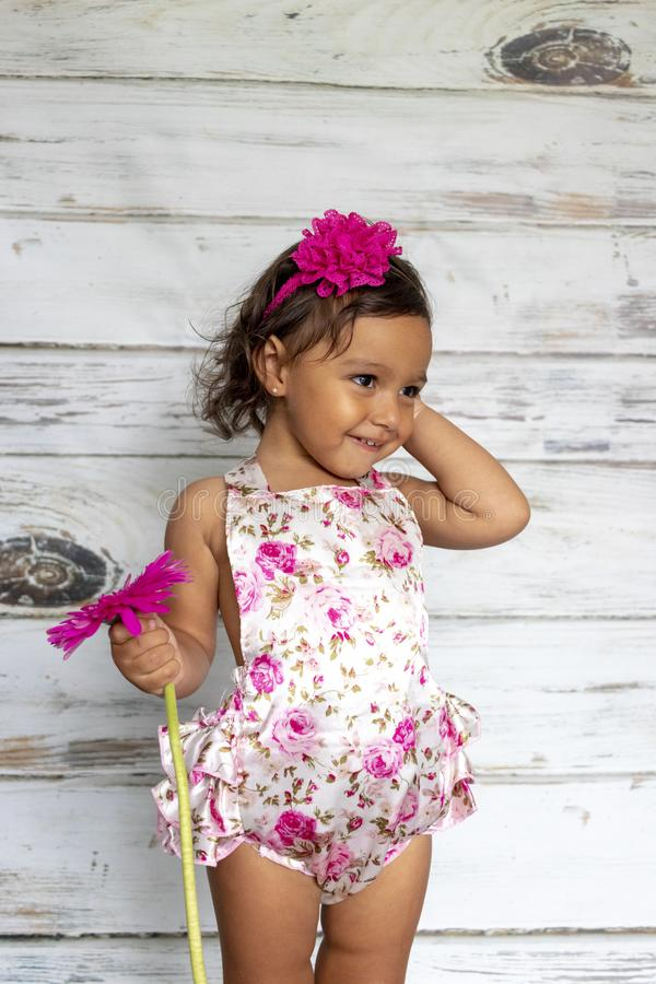Tender smiling toddler. With a flower in her hands royalty free stock photos