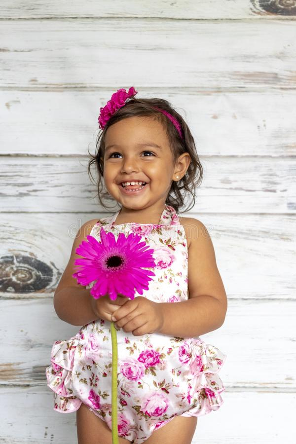 Tender smiling toddler. With a flower in her hands stock photography