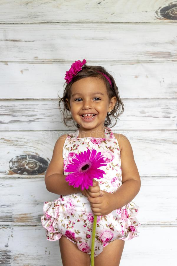 Tender smiling toddler. With a flower in her hands stock images