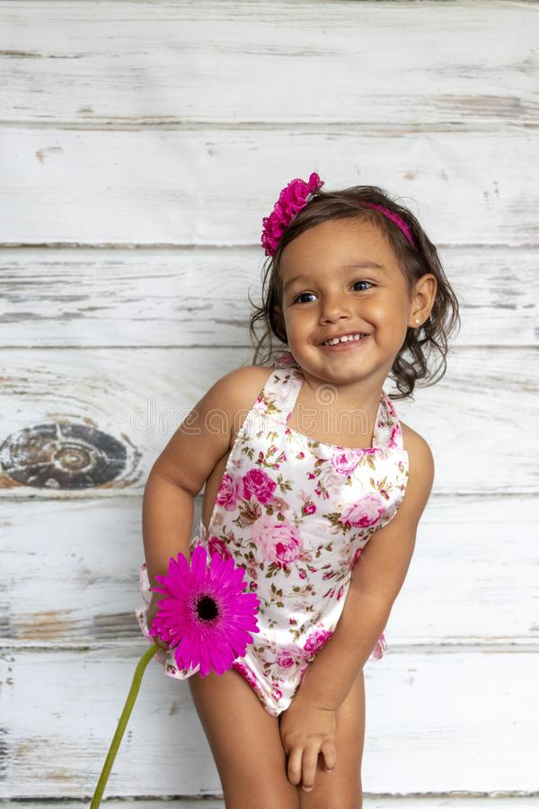 Tender smiling toddler. With a flower in her hands royalty free stock image
