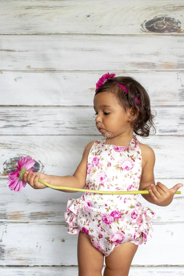 Tender smiling toddler. With a flower in her hands royalty free stock photo