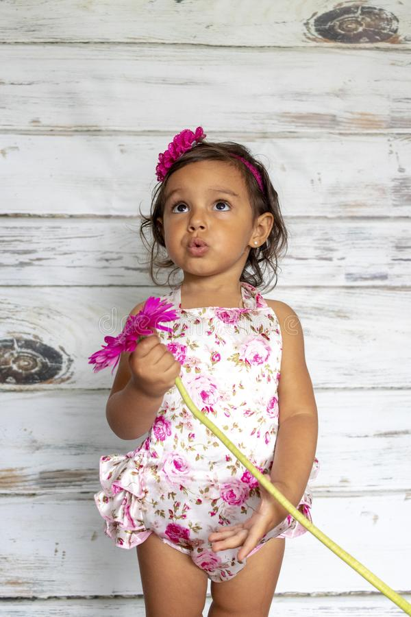 Tender smiling toddler. With a flower in her hands stock image