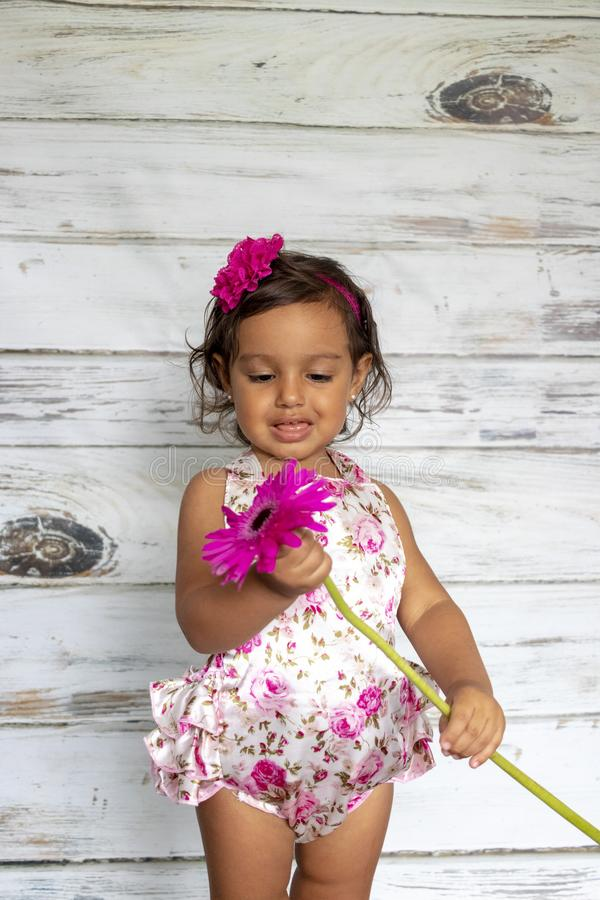 Tender smiling toddler. With a flower in her hands stock photos