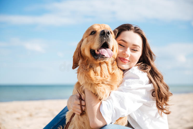 Tender smiling young woman hugging her dog on the beach stock images