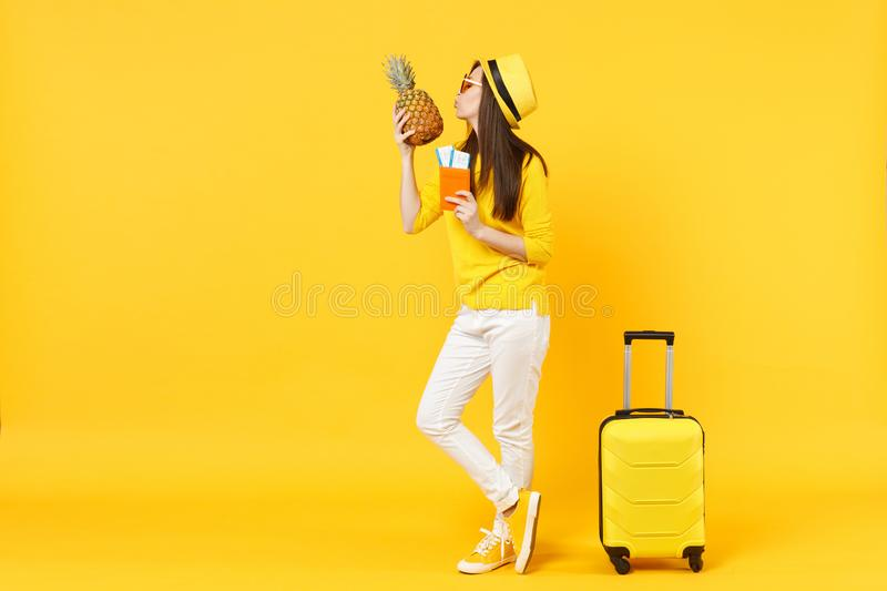 Tender traveler tourist woman in hat holding passport tickets, kissing pineapple fruit isolated on yellow orange. Background. Passenger traveling abroad on royalty free stock photography