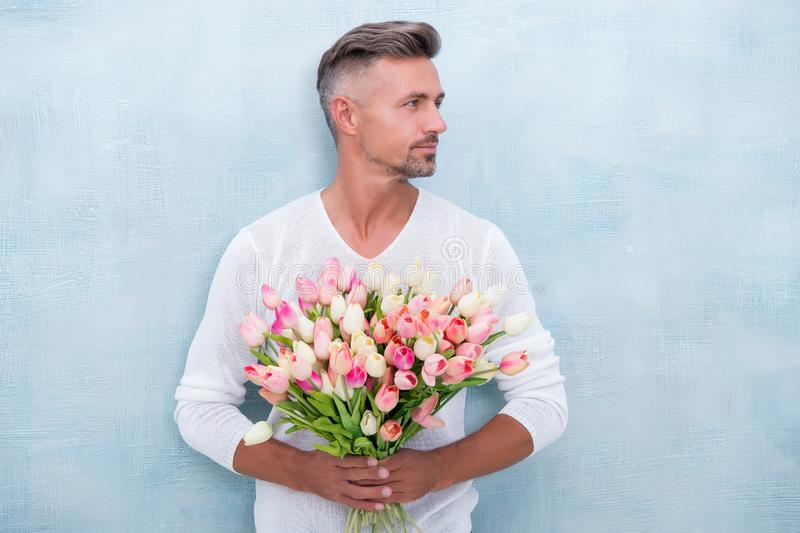 Tender tulips for her. For someone special. Man with tulips bouquet. Handsome man holding pink tulips. Attractive man royalty free stock photo