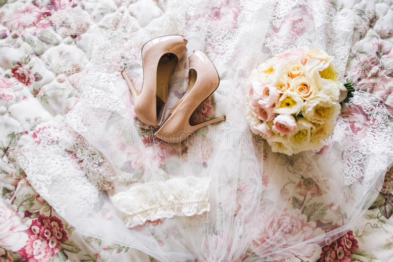 Tender wedding veil, shoes, wedding garter and flowers bouquet, top view stock photo