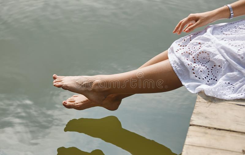 Tender women`s feet on the river bank. royalty free stock photo