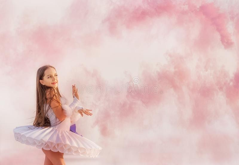 Tender young ballerina dancer in a snow-white tutu dress and white pointe shoes in pink smoke. stock photo