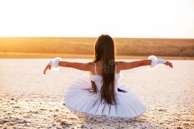 Tender young ballerina dancer in a snow-white tutu dress and white pointe shoes on a salty dried lake. stock images