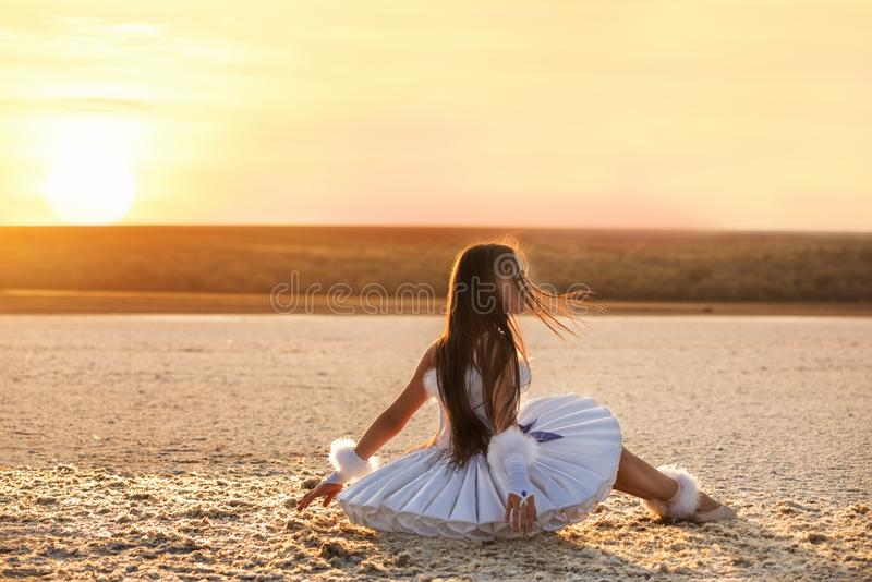 Tender young ballerina dancer in a snow-white tutu dress and white pointe shoes on a salty dried lake. stock image