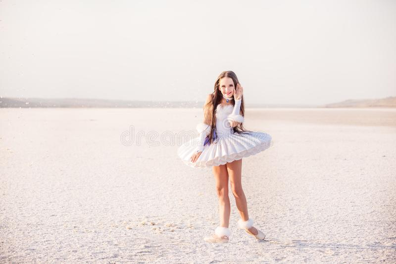 Tender young ballerina dancer in a snow-white tutu dress and white pointe shoes on a salty dried lake. Fantastic landscape and a g royalty free stock photos