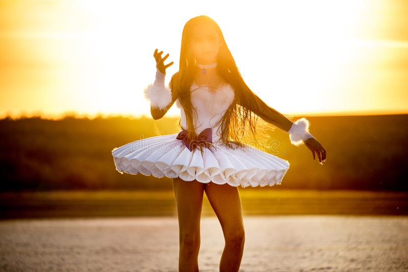 Tender young ballerina dancer in a snow-white tutu dress and white pointe shoes on a salty dried lake. royalty free stock photography