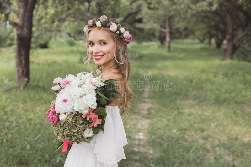 tender young bride in floral wreath and wedding dress holding bouquet of flowers and smiling at camera outdoors stock images