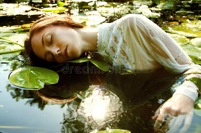 Tender young woman swimming in the pond among water lilies. Basking in the sun in shallow waters stock photos