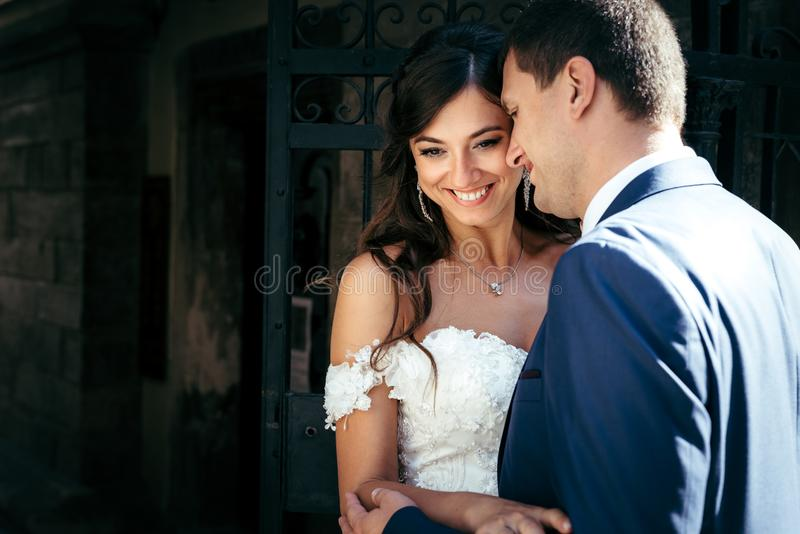 Tenderly hugging smiling newlywed couple. Emotional close-up wedding outdoor portrait. stock images