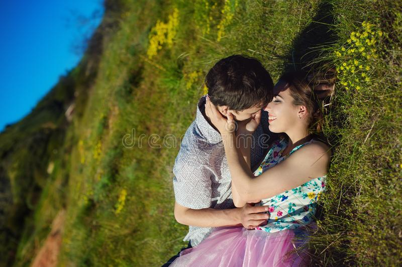 Tenderly kissing couple. Man and woman lying towards down. Kiss on the cheek stock photo