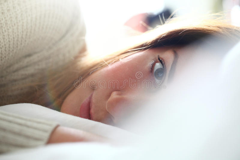 Tenderness in bed. Look of woman lying between the sheets. Close portrait of the face of a young woman lying in bed. Selective focus on the eye. Concept of royalty free stock photo