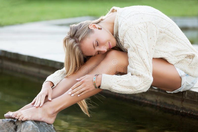 Tenderness. Charming girl in sweater near the water royalty free stock images
