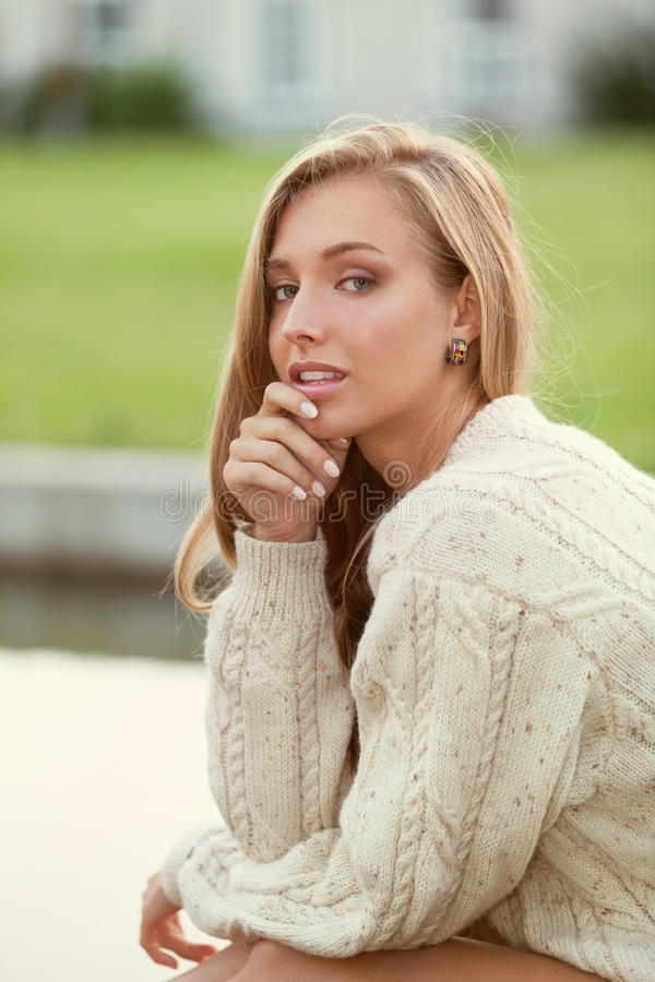 Tenderness. Charming girl in sweater near the water stock image