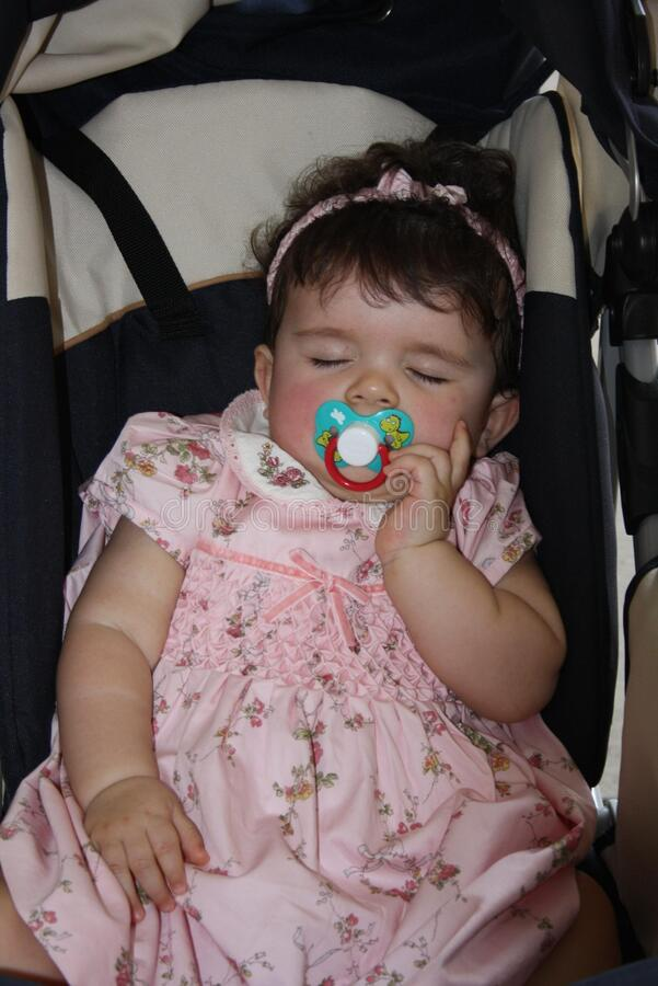 Italy, Milan - May 24, 2009: sweet 1 year old baby sleeping with a pacifier. The tenderness of a little girl with a pink flower dress and a headband that sleeps stock photo