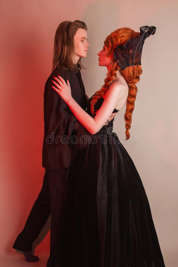 Tenderness in a relationship. Gothic couple dancing in halloween clothes. Redhead woman in dress. Vampire couple on dark backgroun stock image