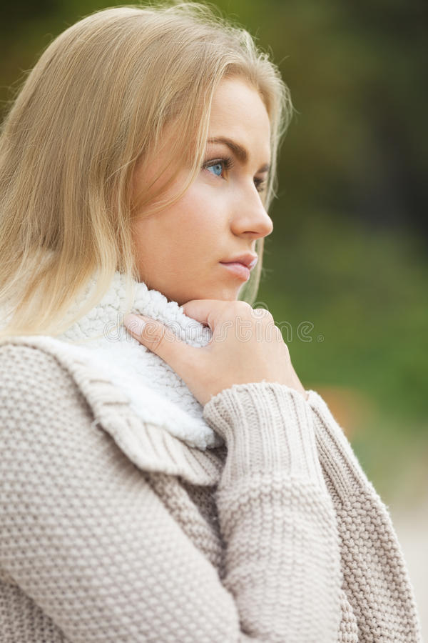 Tenderness. Thinking cute blond girl outdoors stock photo