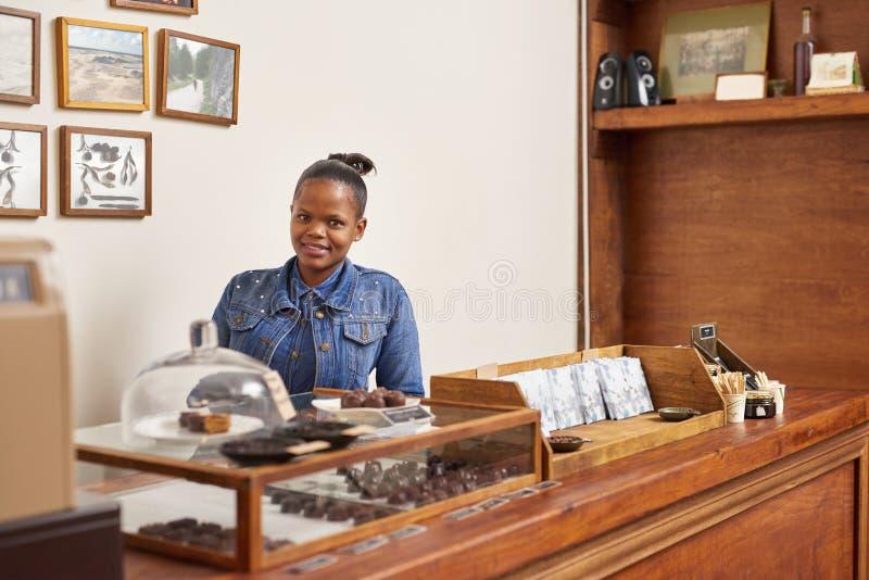 Tendero artesanal del chocolate que sonríe mientras que se coloca detrás de su contador fotografía de archivo libre de regalías