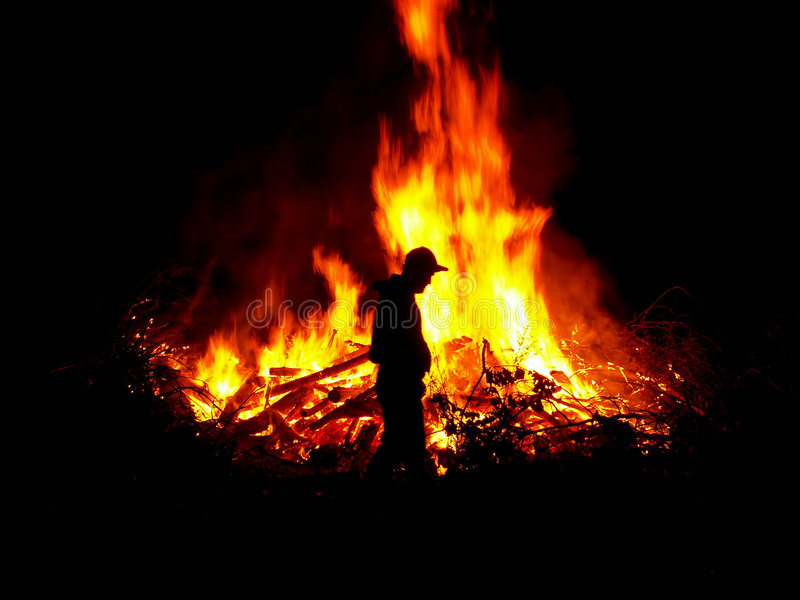 Tending the fire. Man's profile against a large fire royalty free stock photography