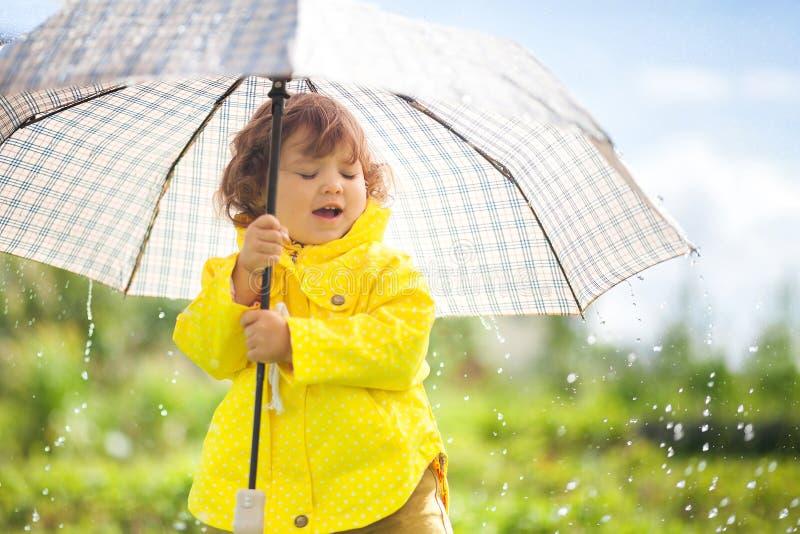 Tendo o divertimento sob a chuva, menina da criança com guarda-chuva imagem de stock