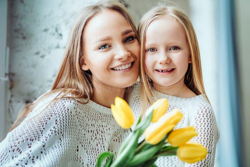 Tendo o melhor dia com mamã Mãe e filha junto com o ramalhete das tulipas imagens de stock royalty free