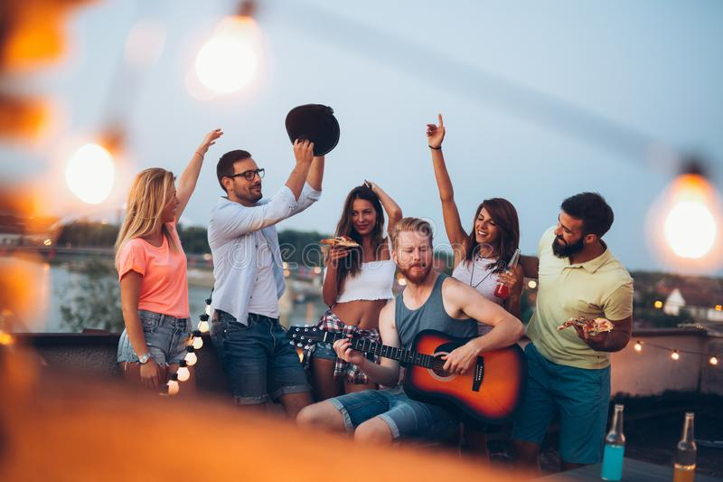 Tendo uma grande estadia com amigos, divertimento do havinf no partido do telhado fotografia de stock