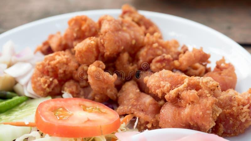 Tendones fritos del pollo en el cierre blanco del plato para arriba con vagos de madera foto de archivo