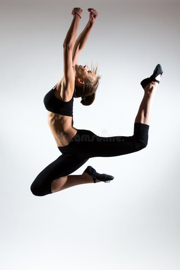 Tendresse, grâce, mélodie et plastique de fille gymnastique Honorez le saut dans le ciel de la gentille jeune fille photo libre de droits
