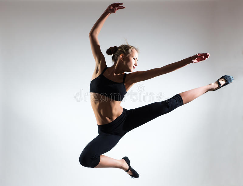 Tendresse, grâce, mélodie et plastique de fille gymnastique Honorez le saut dans le ciel de la gentille jeune fille images libres de droits