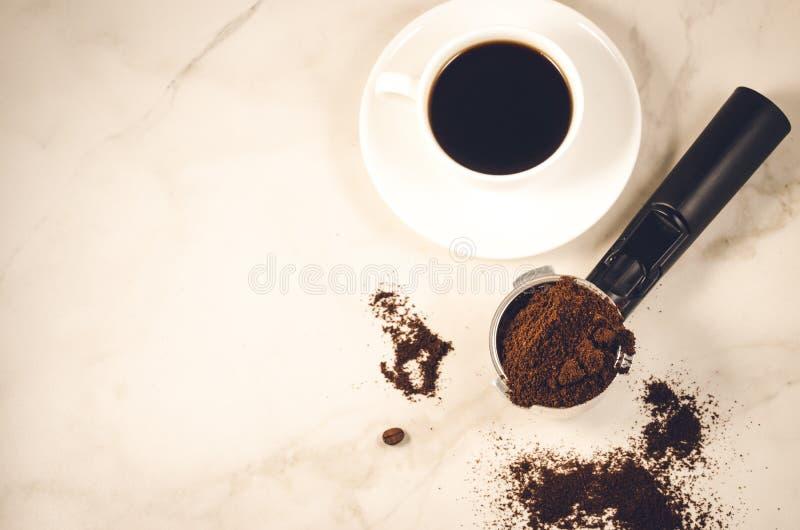 tenedor llenado del café molido y de una taza blanca/tenedor llenado del café molido y de una taza blanca en un fondo de mármol V imagenes de archivo