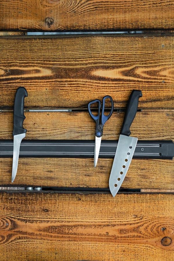 Tenedor magnético del cuchillo en una pared de madera fotografía de archivo