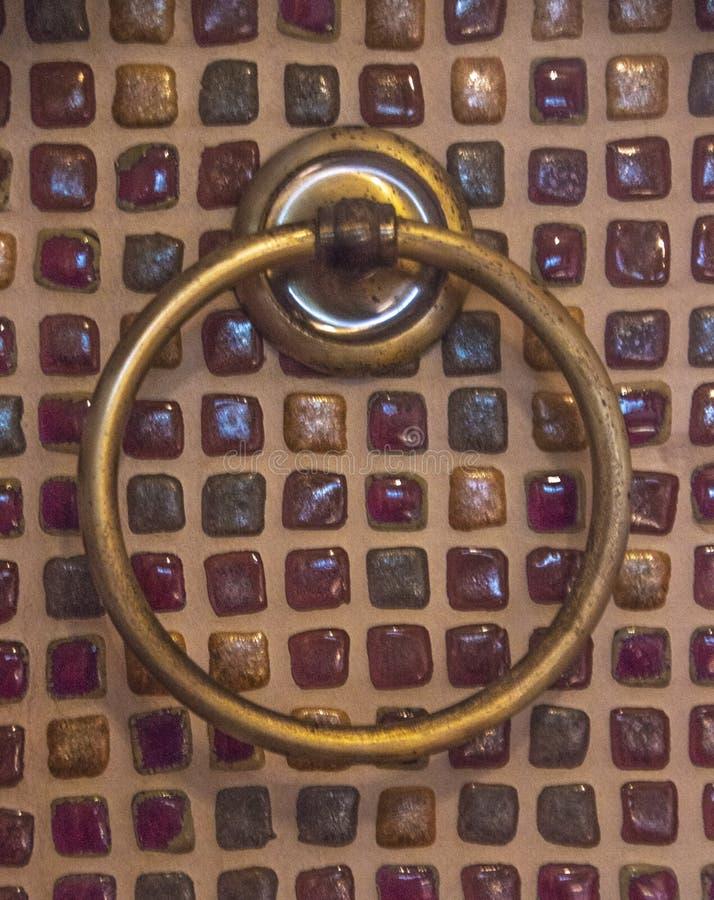 Tenedor rústico de la toalla del amarillo-cobre del metal viejo en la pared foto de archivo