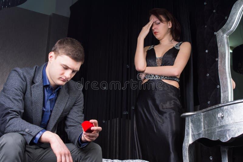 Teneergeslagen jonge mens die de ringsdoos bekijken stock afbeelding