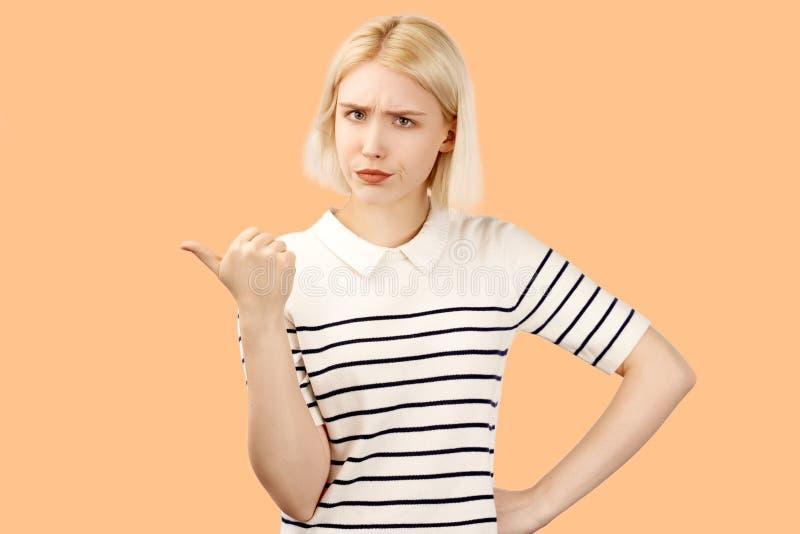 Teneergeslagen meisjesfrown, voelt ongelukkig, richt met wijsvinger leftward, is niet bevallen zie ??n of ander punt royalty-vrije stock fotografie