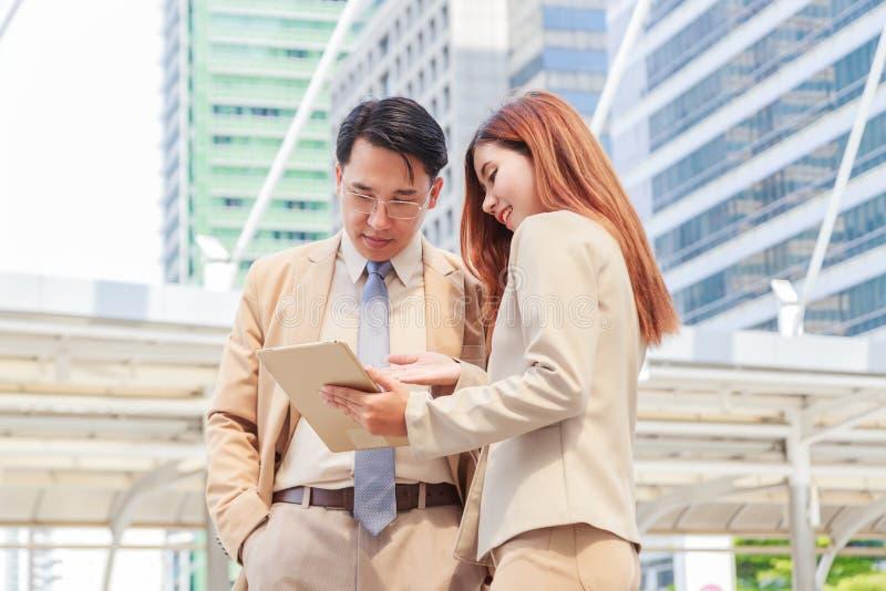 ¡Tenemos ya grandes resultados! Mujer hermosa joven que señala en la tableta con sonrisa y que discute algo con su jefe mientras  fotos de archivo libres de regalías
