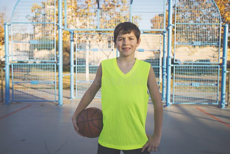 Tenencia adolescente alegre un baloncesto en la corte fotos de archivo