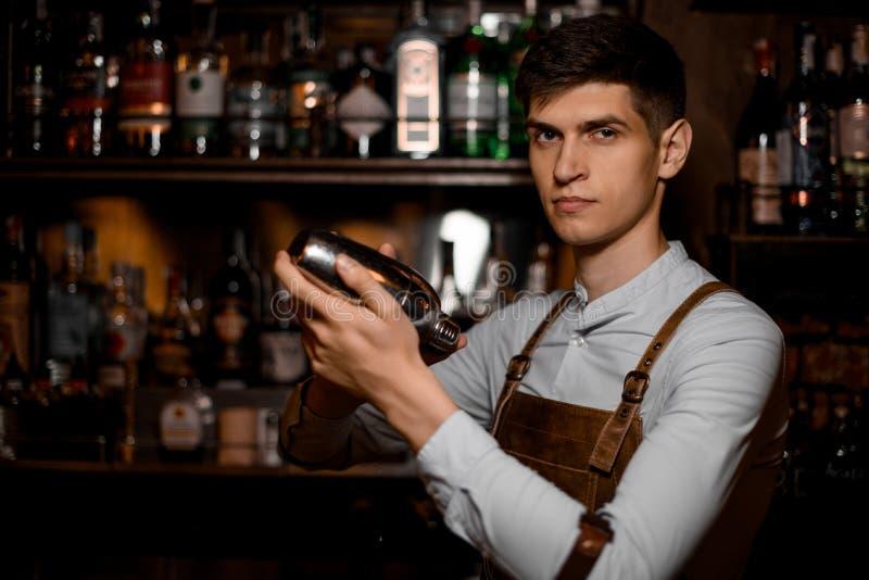 Tenencia atractiva del camarero en manos una coctelera de acero imagen de archivo libre de regalías