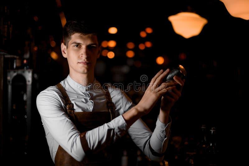 Tenencia atractiva del camarero en manos una coctelera de acero en la oscuridad foto de archivo