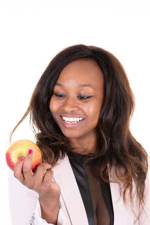 Tenencia brasileña de la mujer negra que mira el concepto afroamericano rojo de Apple imagenes de archivo