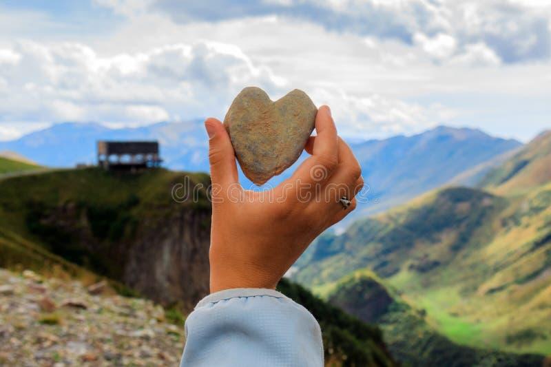 Tenencia de brazo la piedra en forma de corazón delante de la vista amplia del alto paisaje hermoso de las montañas del Cáucaso e foto de archivo