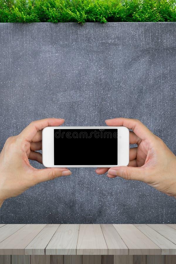 Tenencia de la mano de la mujer y usar el teléfono elegante con la pared aislada de la pantalla y del mármol y el piso de madera  foto de archivo